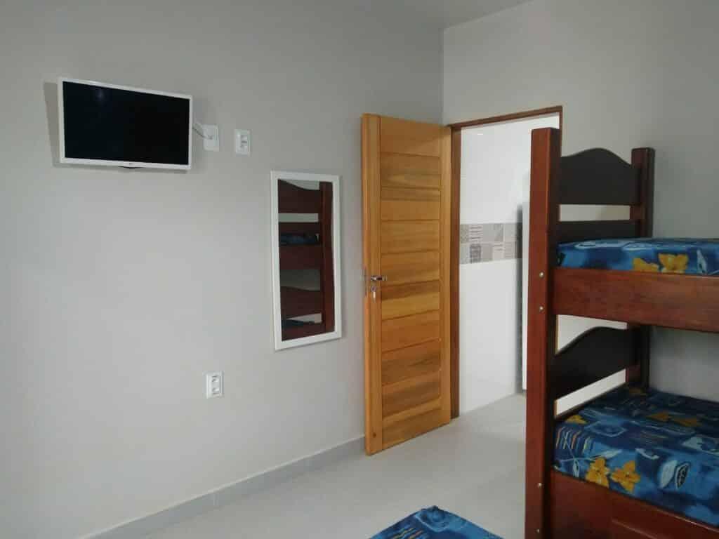 Quarto de Airbnbcom beliche, espelho e TV no Apartamento novo, mobiliado, à 700 mts da praia de Tabatinga