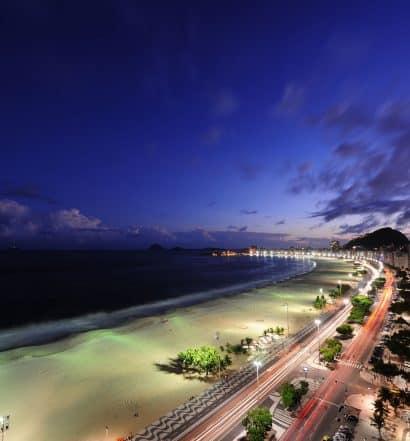 """Orla de Copacabana com calçadão de desenho icônico, ao anoitecer, ilustrando post """"onde ficar em Copacabana"""""""