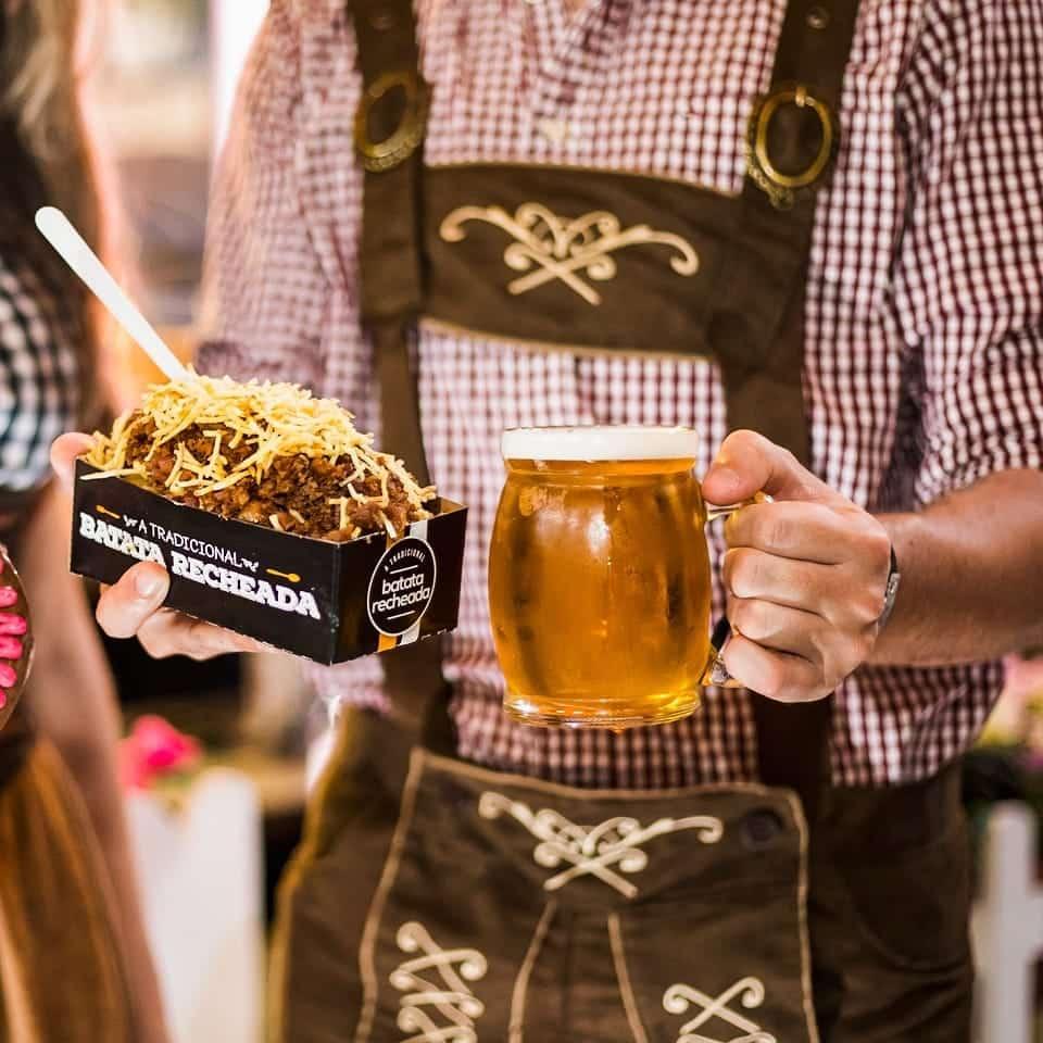Pessoa segurando batata recheada e cerveja gelada na Oktoberfest