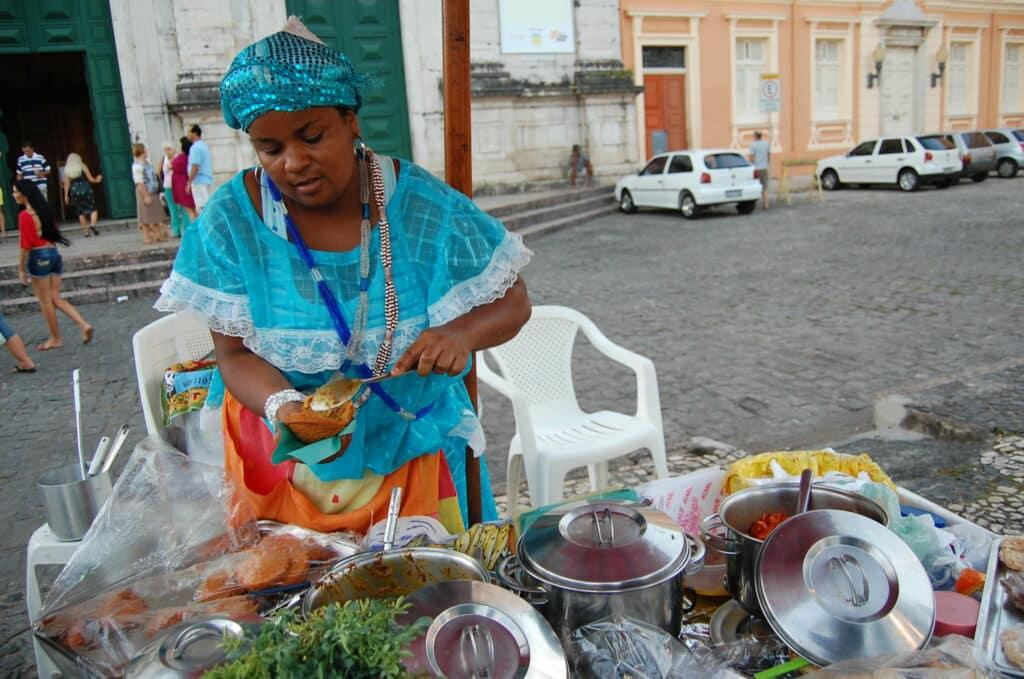 Baiana preparando acarajé em barraquinha de Salvador