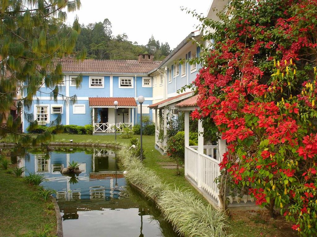 Espaço em Penedo com construções coloridas, lago e árvores floridas