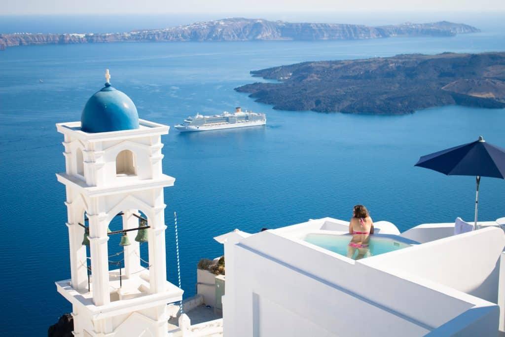 Pessoa em piscina com vista para o mar da Grécia em Imerovigli