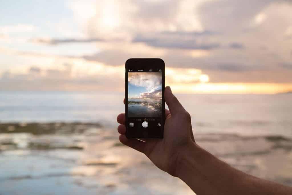 homem tirando foto com iphone na praia