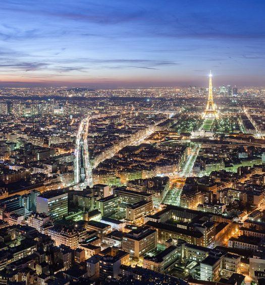 O horizonte de Paris ao anoitecer, com a Torre Eiffel iluminada, na capa do post sobre hotéis perto da Torre Eiffel