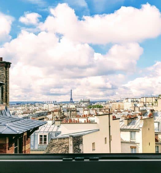 Janela no centro de Paris com vista para a Torre Eiffel, ilustrando post de Airbnb em Paris